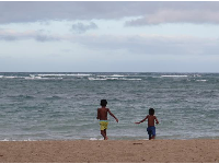 Little boys running toward the water.