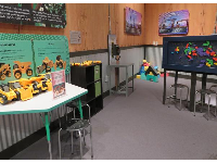Children's area with gears, electronic projects, magnets, and trucks.