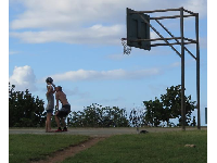 A couple plays basketball in the late evening.
