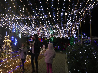 A mom and daughter walk under a canopy of lights.