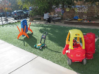 Fire hydrant with hose, little coupe for toddlers, lawn mower, and connect 4, on the grassy area outside.