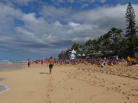 A young man walks along the shore at the Pipeline Masters.
