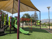 Playground under a huge shade canopy, with mountain views in the distance.