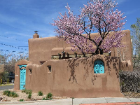 Cute adobe house with blossoming tree and turquoise door.
