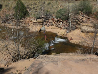 Swimmers standing by tiny falls.