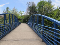 Blue pedestrian bridge at the end of Spring Street, across from the bakery.