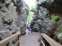 A couple walks between rocks in an exhibit.