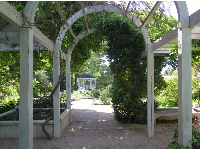 Looking through an arbor toward the gazebo.