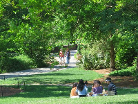 A group sits on the grass while two people stroll in the distance.
