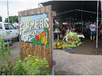 Hilo Farmers Market sign and vegetable stalls.