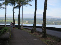 A couple walks along Lihiwai Street, with Mauna Kea in the distance.