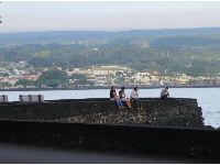 Young people sitting on a rock wall at the bay.