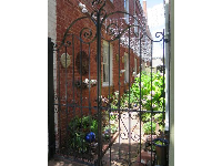 Curlicue ironwork gate and garden.