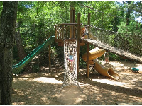 Playground with rope climbey, swinging bridge, and twisty slide.