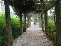 Pergola leading to a tiered fountain.