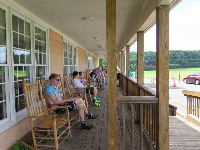 A cyclist relaxes on the front porch in a rocking chair.