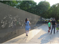 A family walks by pictures of troops etched in the wall.