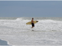 A surfer heads out.