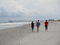 Three young people walk toward the pier.