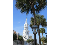 Church steeple, lamppost, and palm trees.