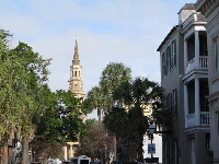Church steeple in the distance, and tall buildings with balconies.