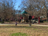 A dad stands with his toddler on the grass in the middle of the play area.