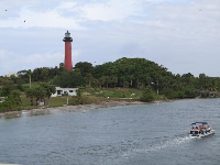 A boat zips by the beautiful Jupiter lighthouse.