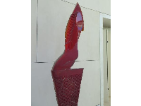 Red Kneeling Figure, by Stephen Dee Edwards. Glass and steel.