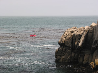 Kayakers paddle around the point.