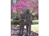 Sculpture of student couple, and purple tree in background, early April.