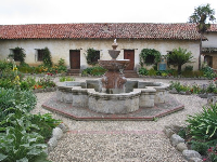Rustic-looking fountain and buildings in front courtyard.