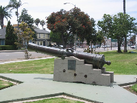 Old Spanish cannon and historical houses behind.