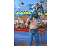 The statue and mural of a father with his son on his shoulders at a fair.