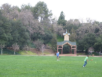 A father and son play ball at Oak Meadow Park, with the lovely hill covered in trees behind.