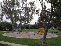 The lower play area, with sand, bouncies, swings, and curvy slide.