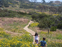 Kids run for joy toward the trail at Sunset Cliffs Natural Park.