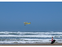 Child with bodyboard, and yellow biplane from Oceano zooming by doing tricks.