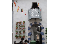Metalwork balcony, flags, pots, and archway at El Andaluz.