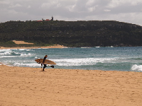 A surfer makes his way to the water.