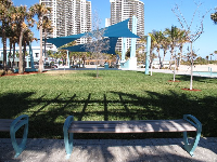 Benches and shade canopy at the park in front of the beach.