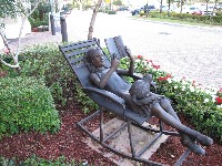Statue of girl leisurely reading a book.