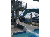 A girl slides down the large, open slide.