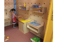 A girl plays quietly in the kitchen area.