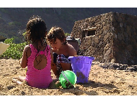 Children play in the sand by the stone bunker-like structure.