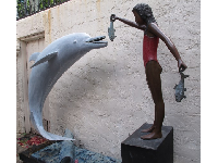 Statue of girl feeding a fish to a dolphin, in Gucci Courtyard.