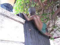 Statue of boy climbing over the wall, in Gucci Courtyard.