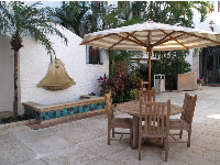 Gorgeous combination of tiled fountain, small palm, wooden table set, and striped umbrella.