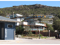 The surf lifesaving club, private homes, and rock formations across from the beach.