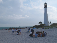 A circle of teens gather on the soft sand.