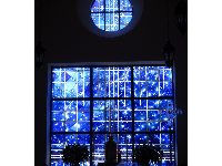 A small side chapel with magical deep blue stained glass depicting the universe.